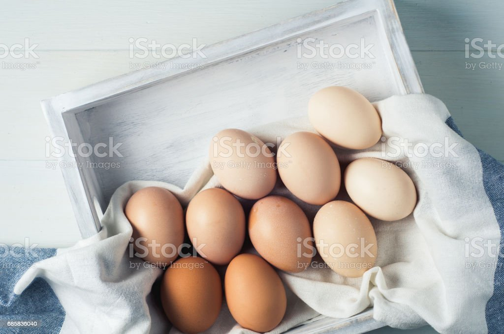 Chicken eggs in a white wooden box on a white background stock photo