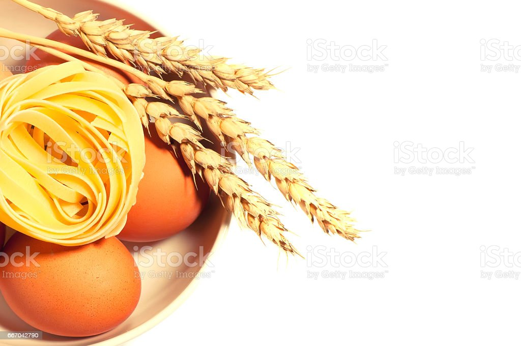 Chicken eggs with wheat spikelets and pasta isolated toned stock photo