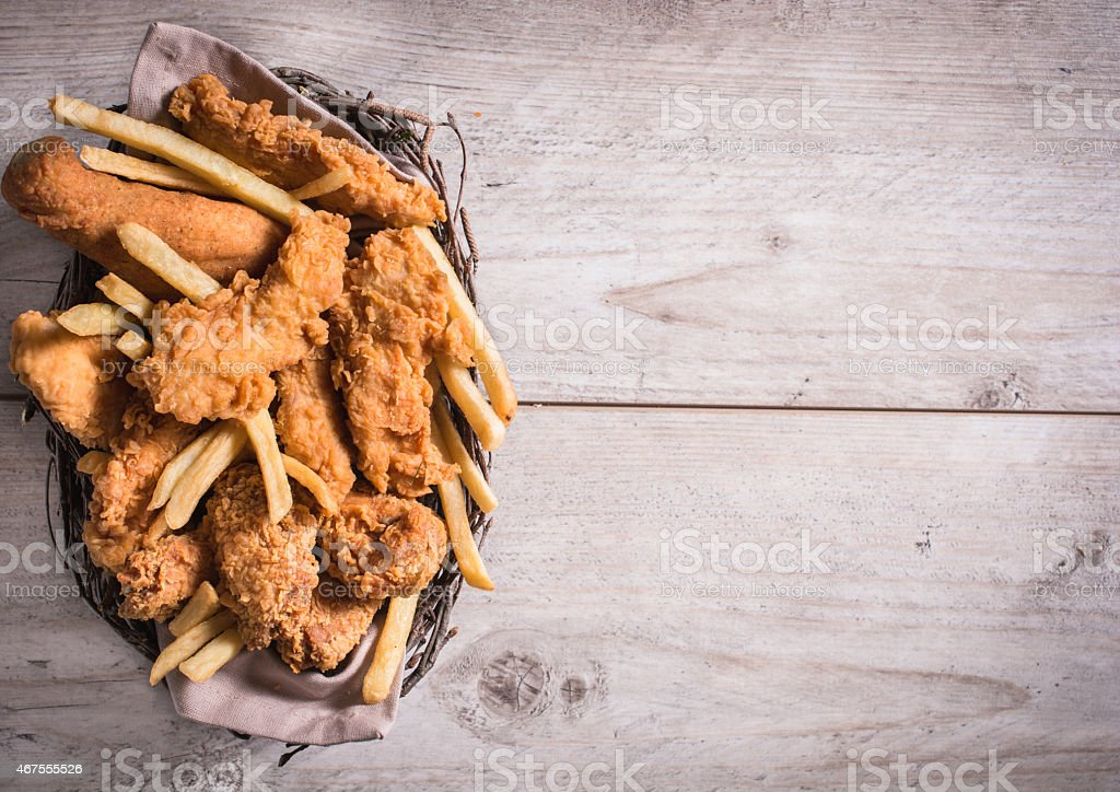 Chicken fingers and fries in a basket on a picnic table stock photo