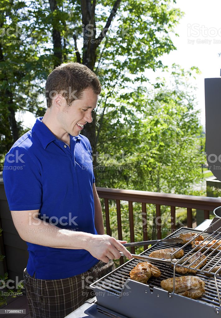 BBQ Chicken Grilling: Caucasian Young Man Smiling on Summer Day royalty-free stock photo
