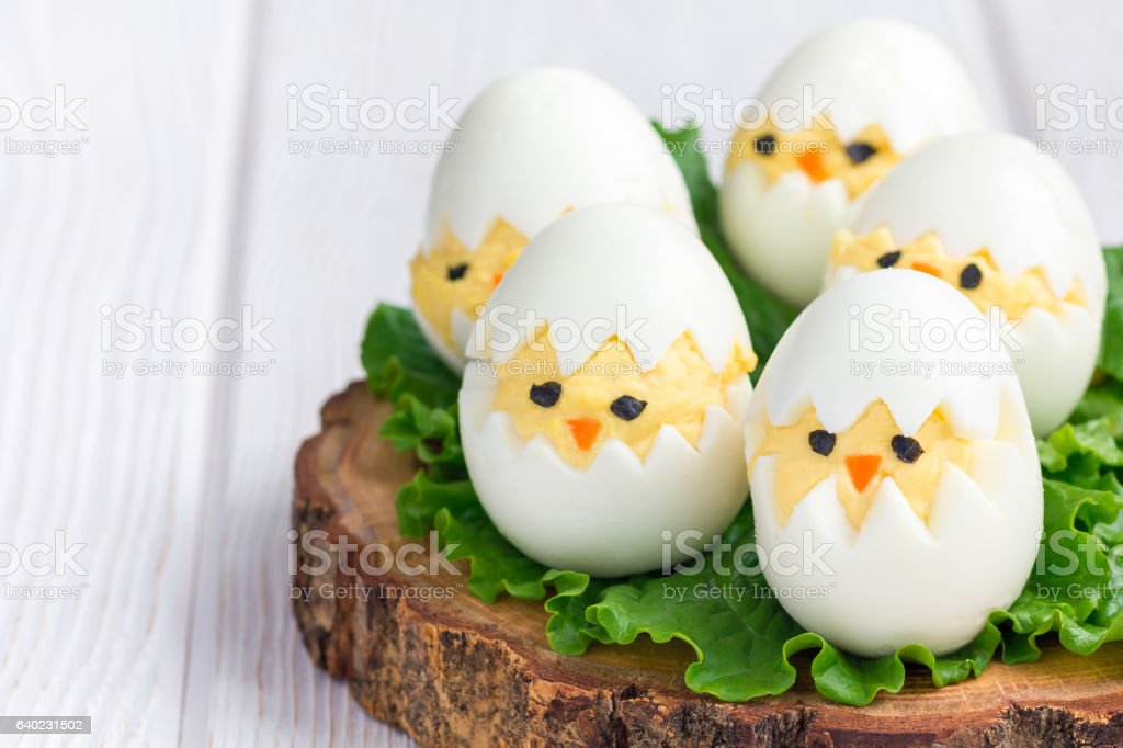 Chicken in nest, deviled eggs on board, horizontal, copy space stock photo