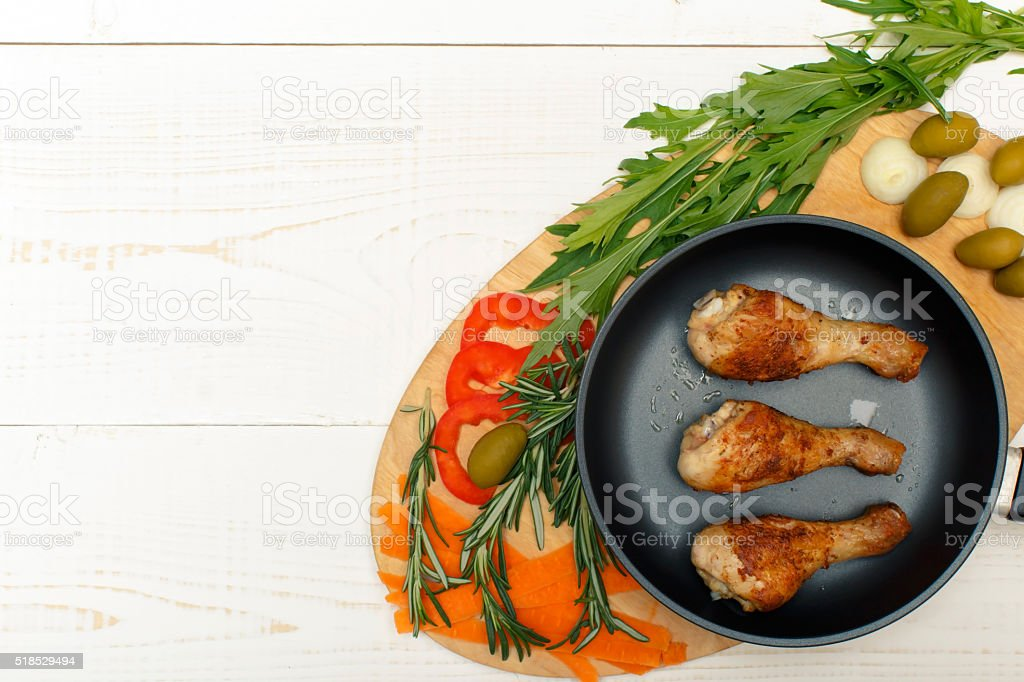 Chicken legs in a pan with vegetables stock photo