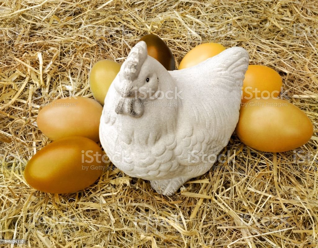 Chicken made of ceramic with golden eggs stock photo