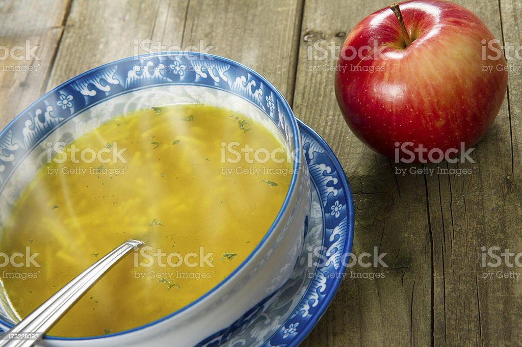 Chicken Noodle Soup And Apple On Wood stock photo