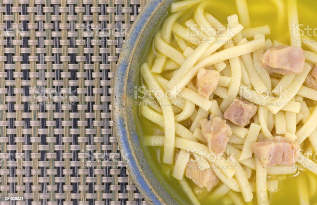 Chicken noodle soup in a bowl top close view stock photo