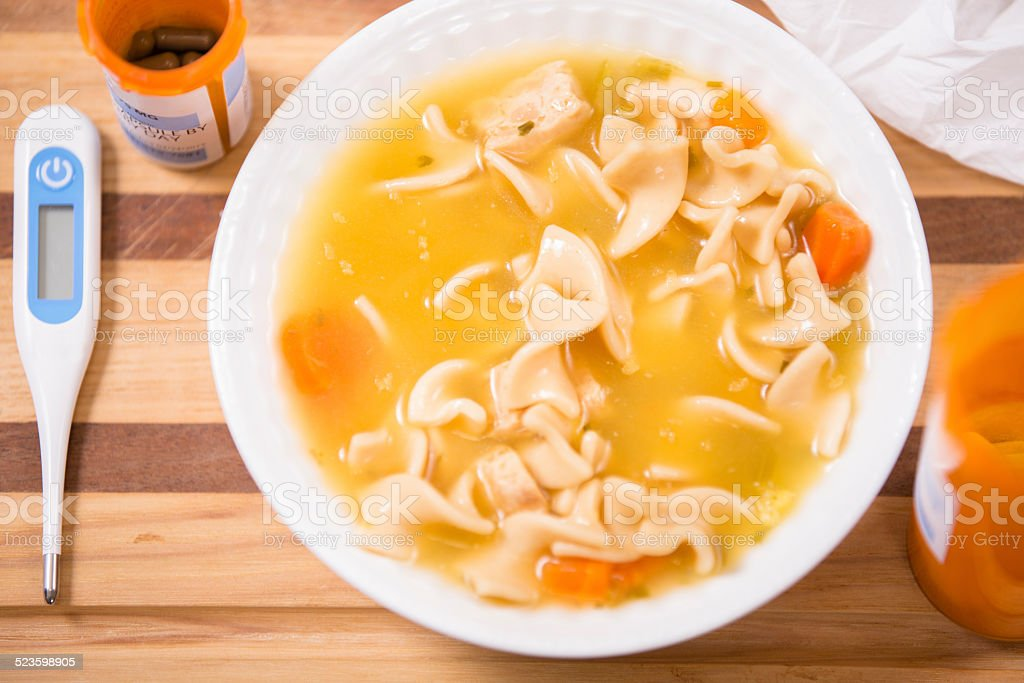 Chicken noodle soup in bowl. Medicines, thermometer. Sick food. stock photo
