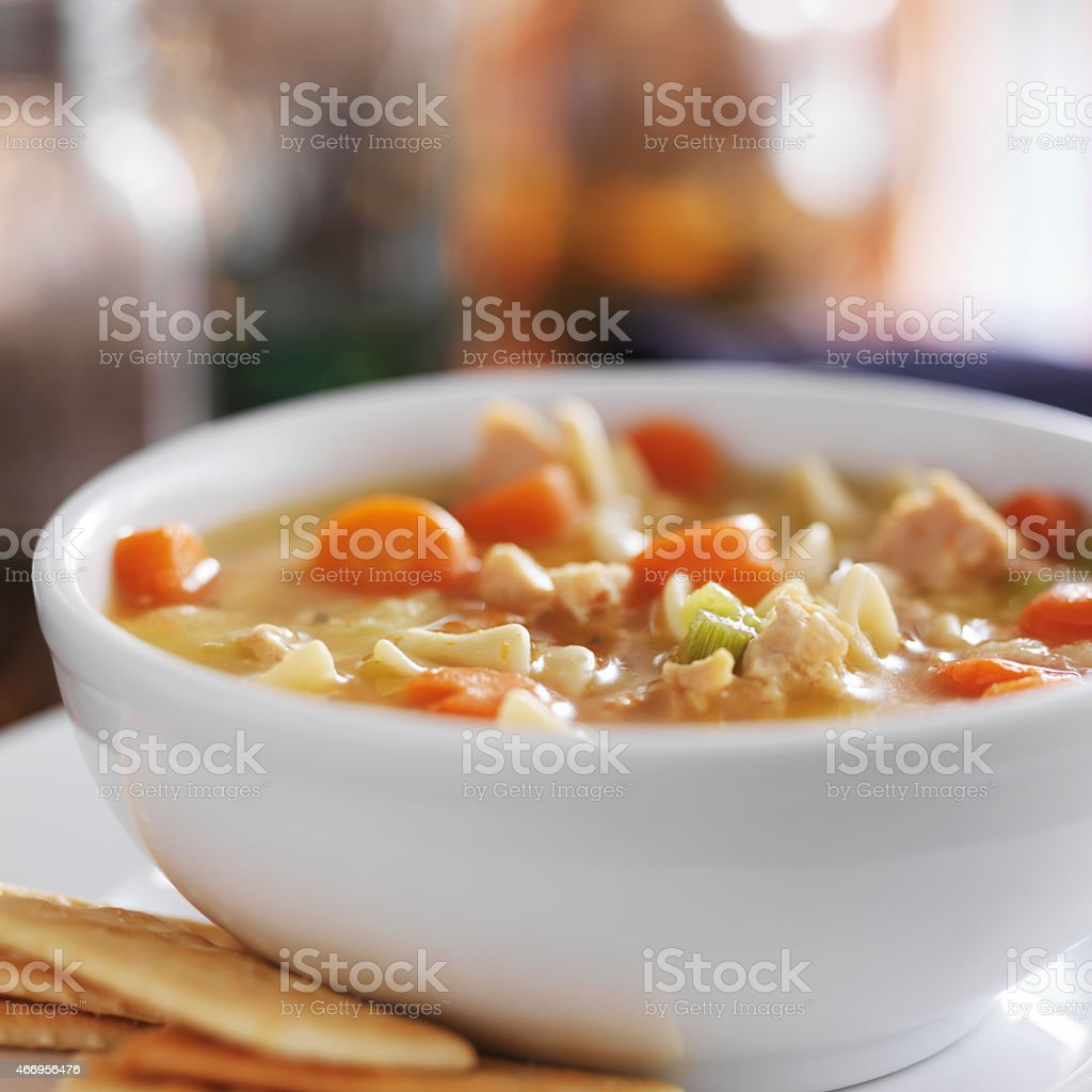 chicken noodle soup with crackers close up stock photo