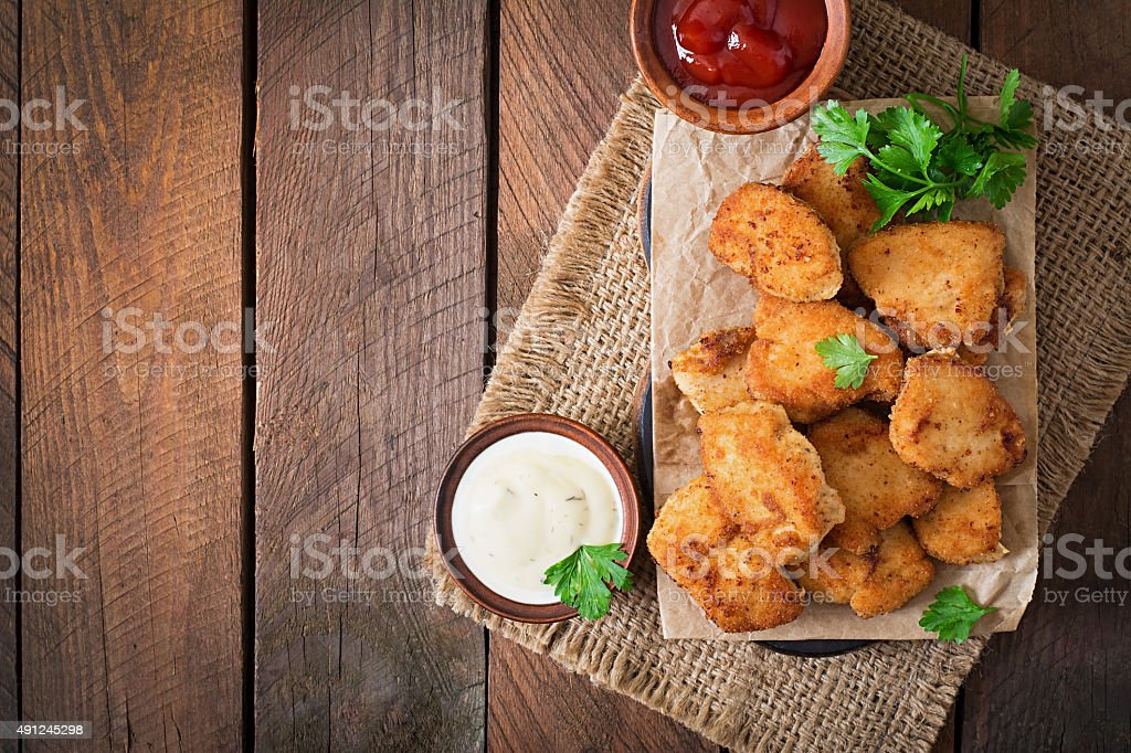 Chicken nuggets and sauce on a wooden background stock photo