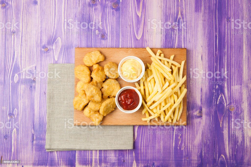 chicken nuggets, French fries and two cups with ketchup and cheese on the table stock photo