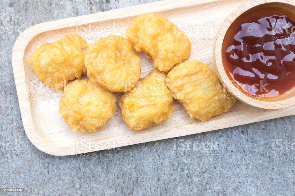 Chicken nuggets on a wooden plate on a rustic background stock photo