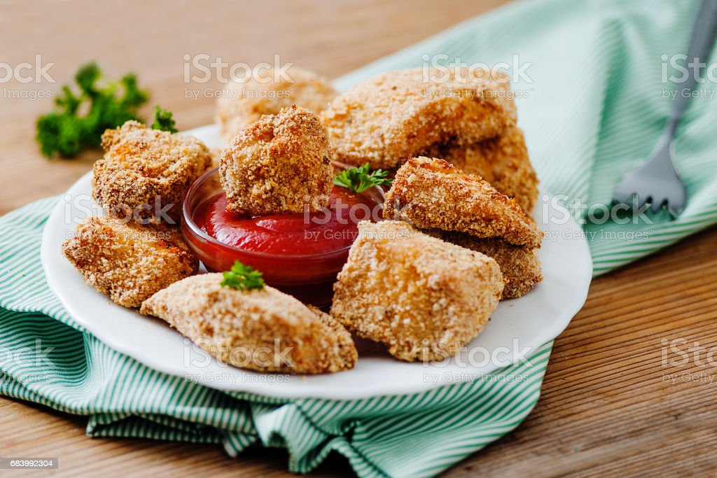 Chicken nuggets on the white plate with tomato sauce stock photo