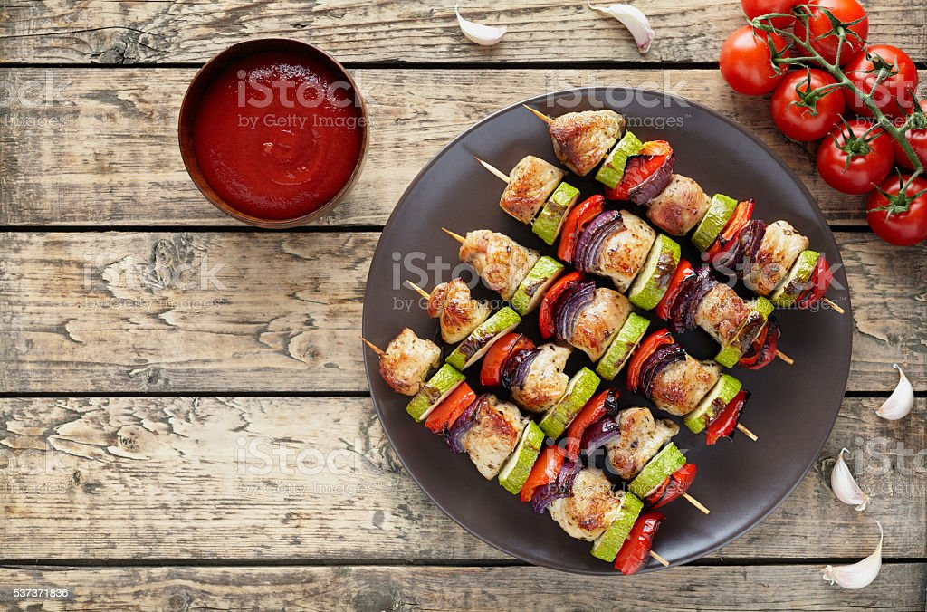 Chicken or turkey meat kebab skewers with ketchup, tomatoes stock photo