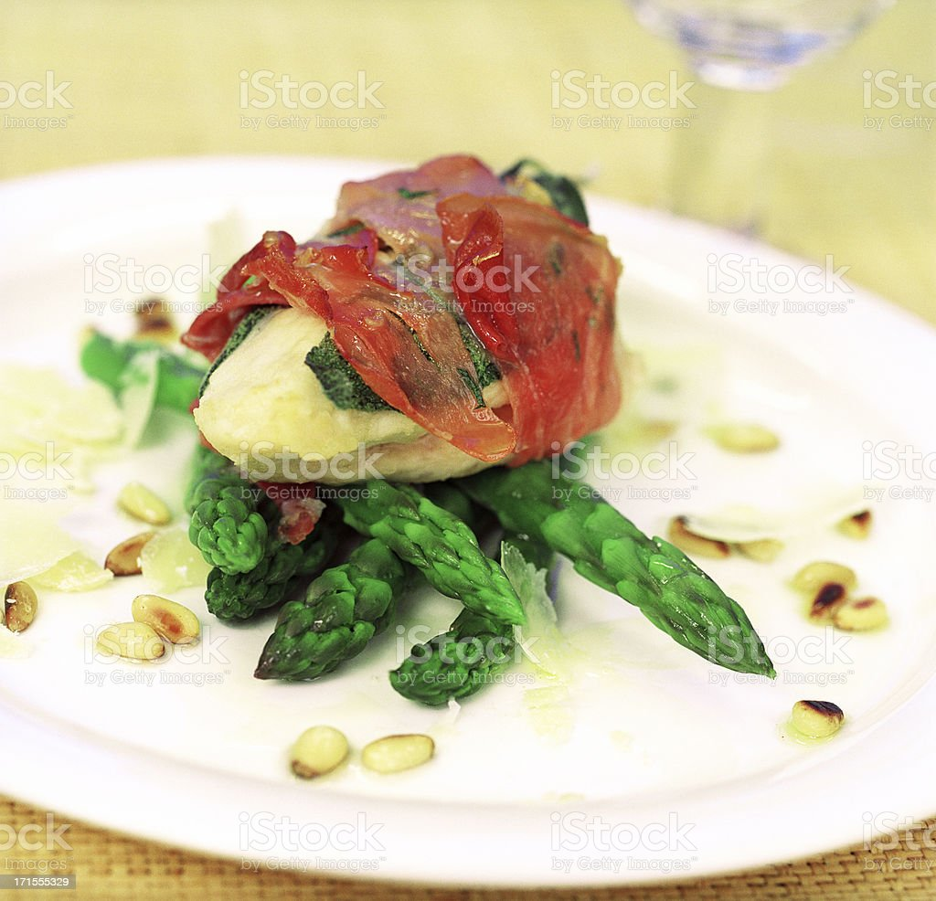 Chicken, parma ham, asparagus and pine nuts stock photo