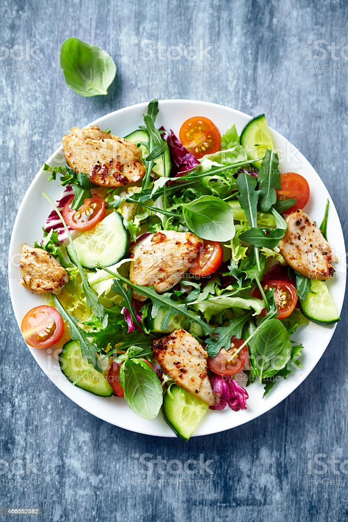 Chicken salad with leaf vegetables and cherry tomatoes stock photo