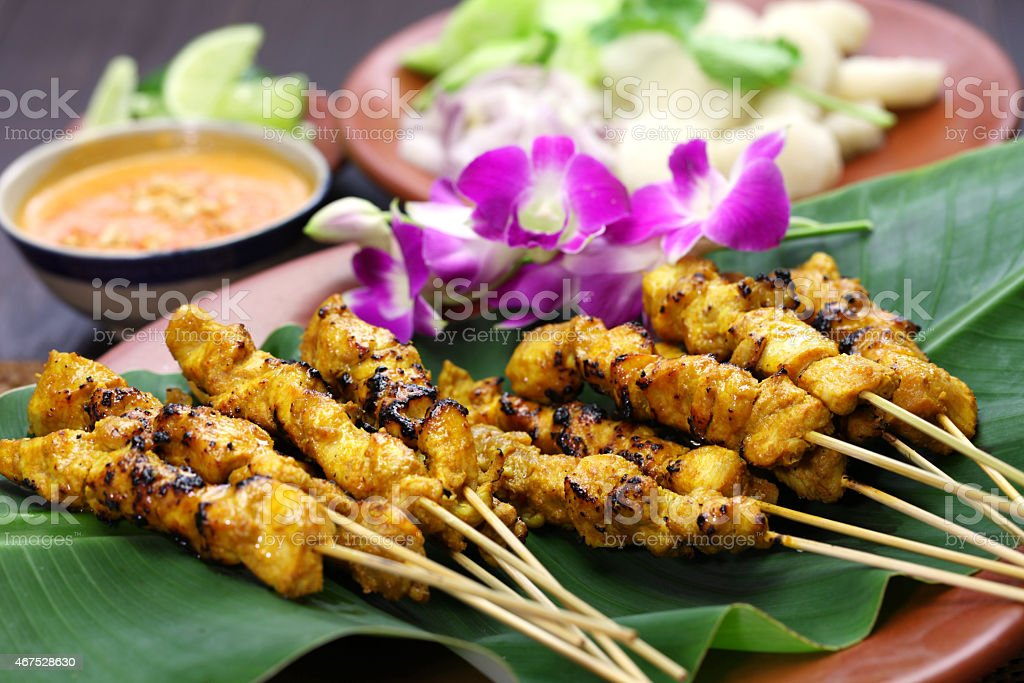 Chicken satay on a banana leaf with purple orchids stock photo