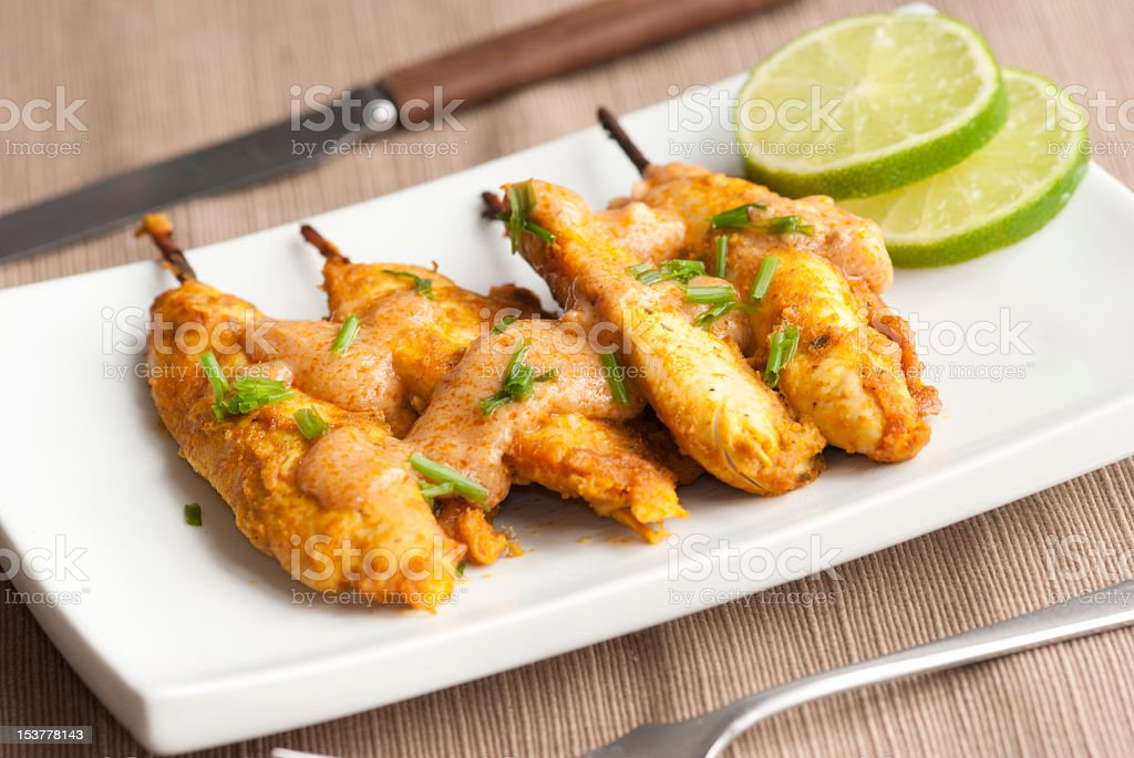 Chicken satay served with fresh lime on white plate stock photo