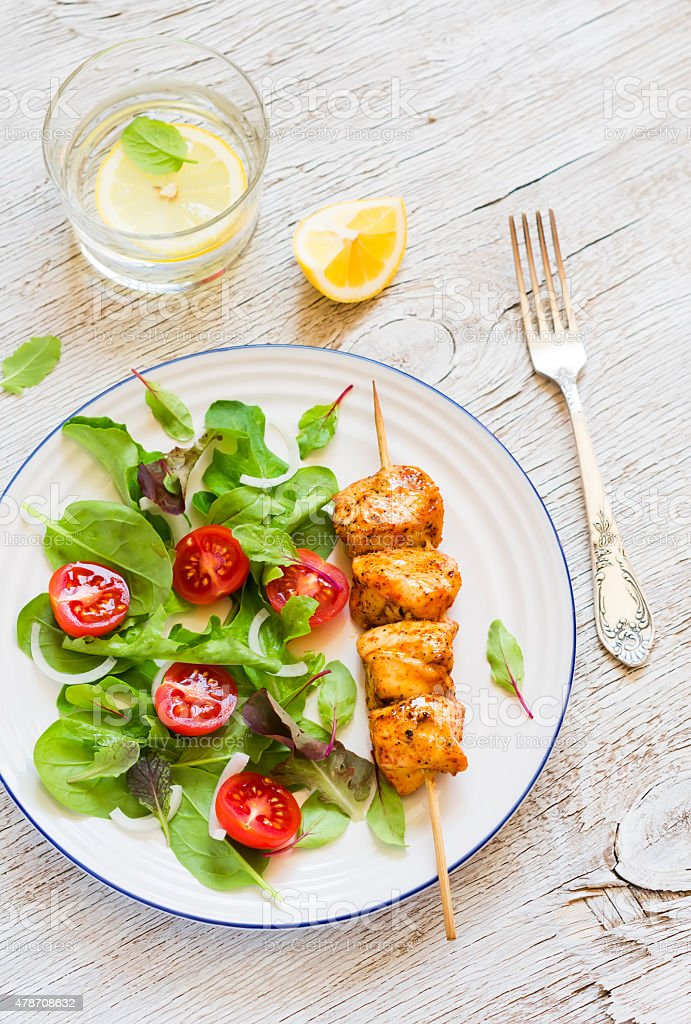 chicken skewers and fresh vegetable salad with cherry tomatoes and spinach stock photo