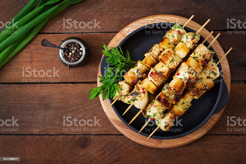 Chicken skewers with slices of apples and chili stock photo