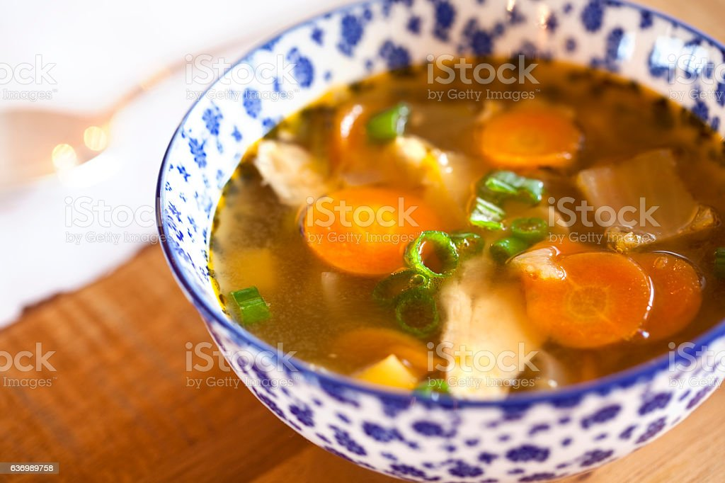 Chicken soup in a white and blue bowl stock photo