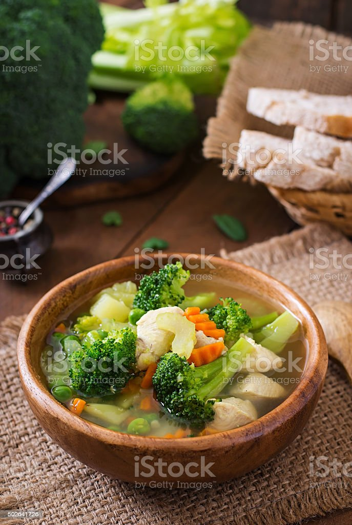 Chicken soup with broccoli, green peas, carrots and celery stock photo