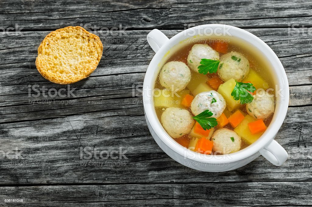 chicken soup with meatballs, carrot and potato sprinkled with p stock photo
