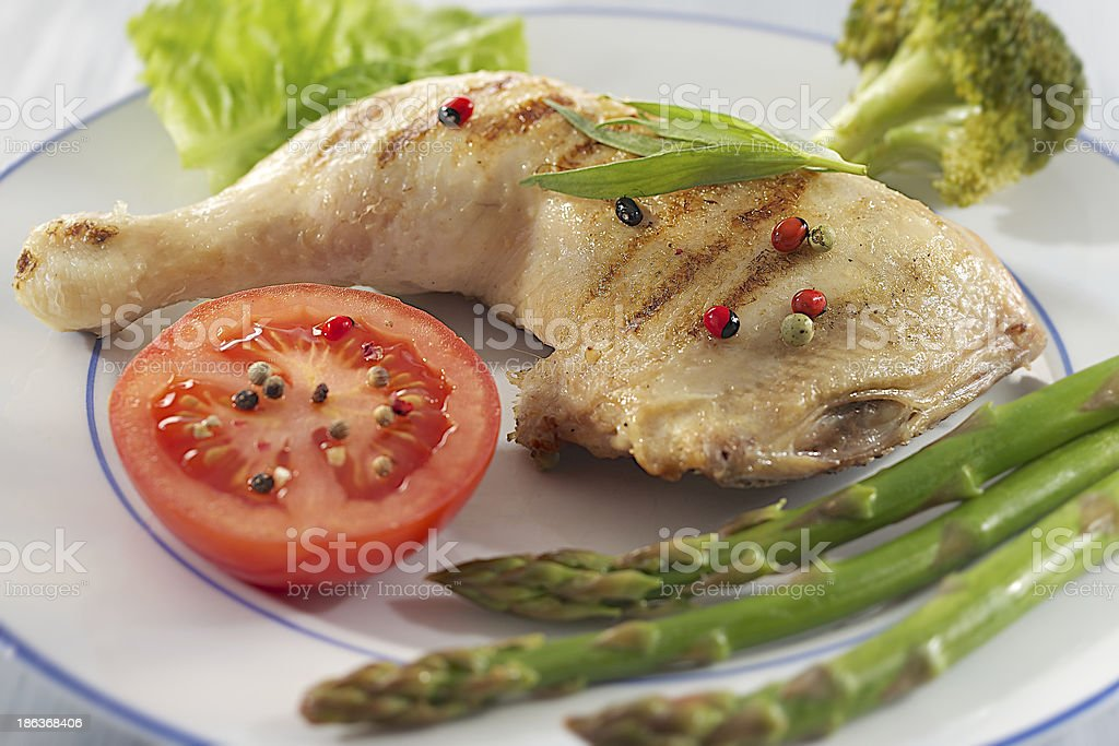 Chicken thigh accompanied by vegetables stock photo