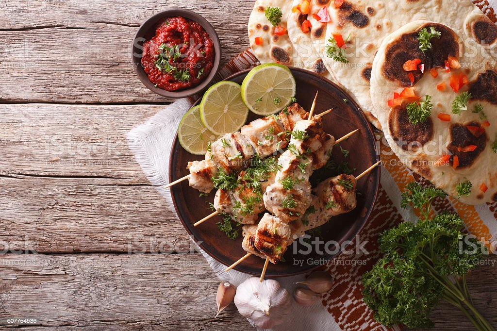 Chicken tikka on skewers, flat bread and chutney. Horizontal stock photo