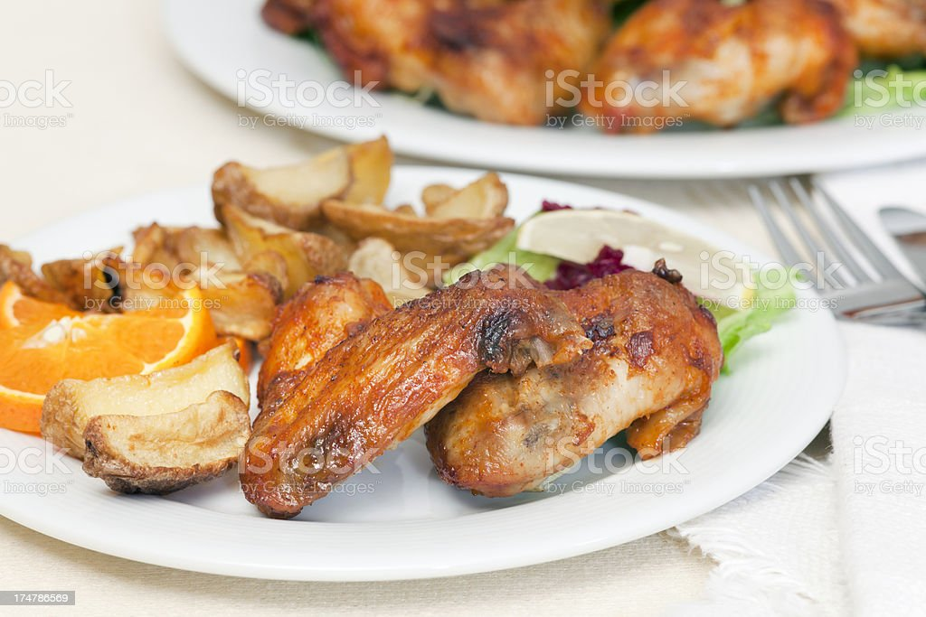 Chicken wings with fried potatoes and garnish on plate stock photo