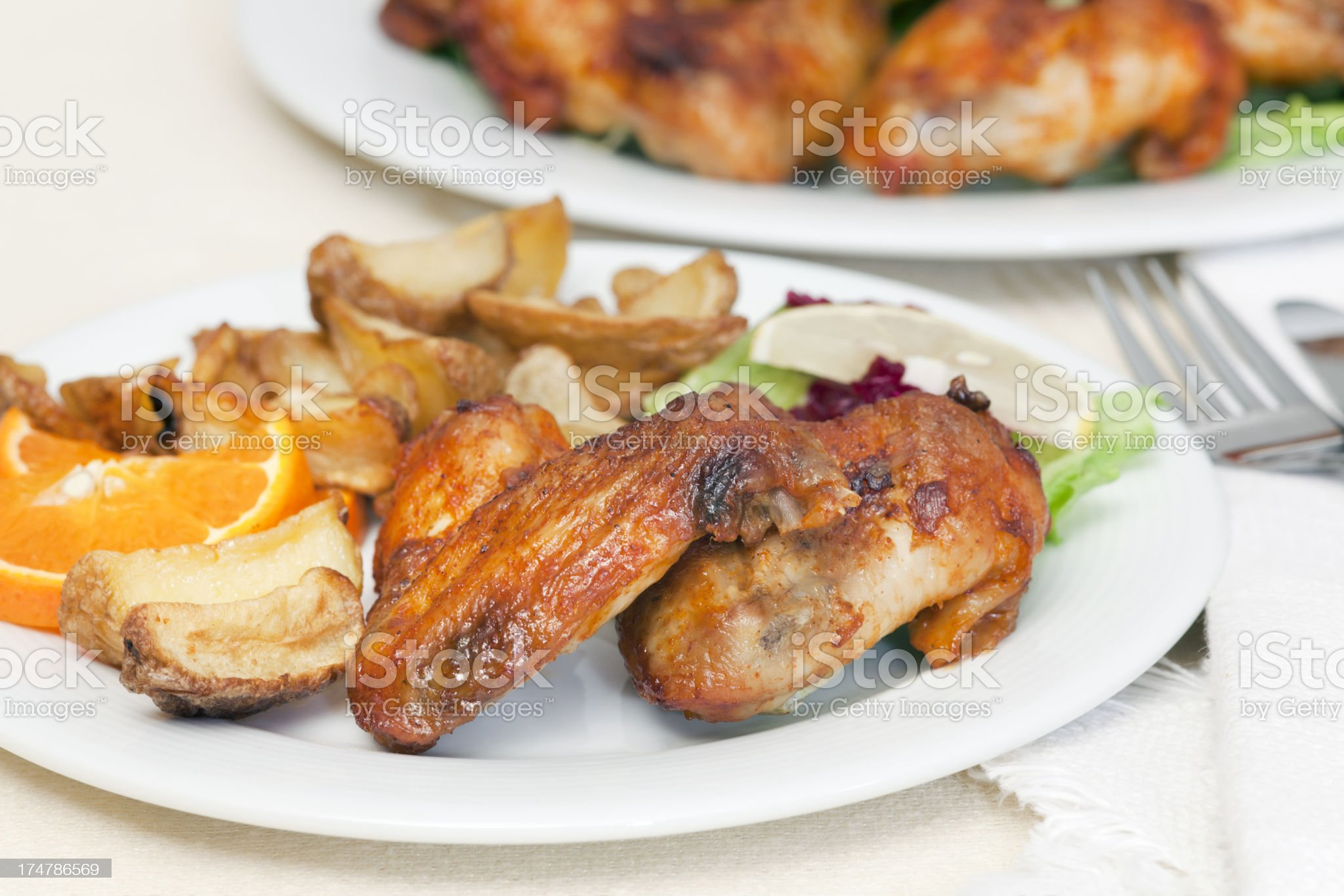Chicken wings with fried potatoes and garnish on plate royalty-free stock photo