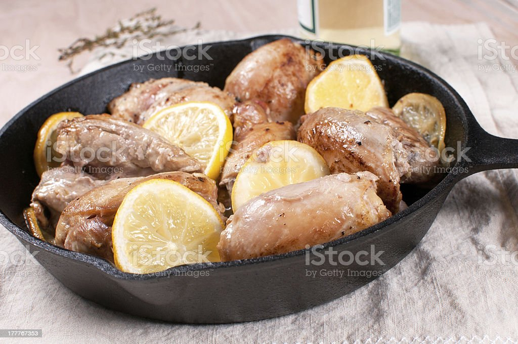 Chicken with lemon slices, wine and herbs stock photo