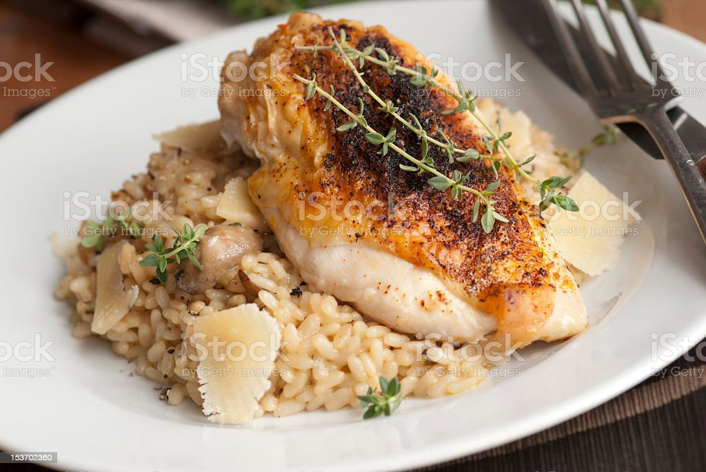 Chicken with risotto on a white plate stock photo