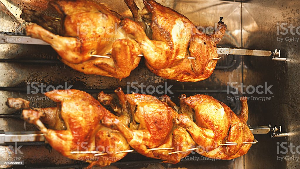 Chickens roasting in rotisserie. stock photo