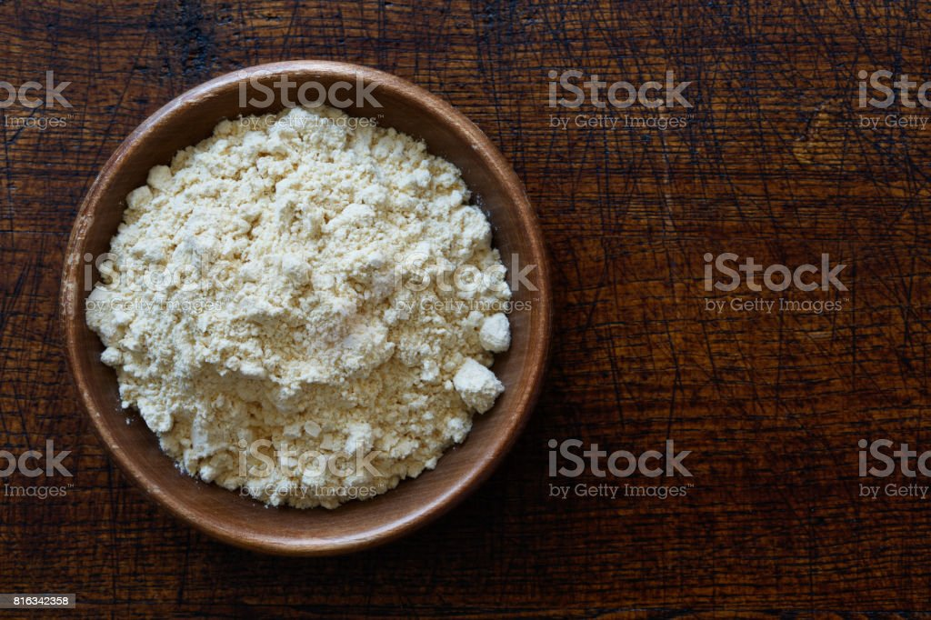 Chickpea flour in dark wooden bowl isolated on dark brown wood from above. stock photo