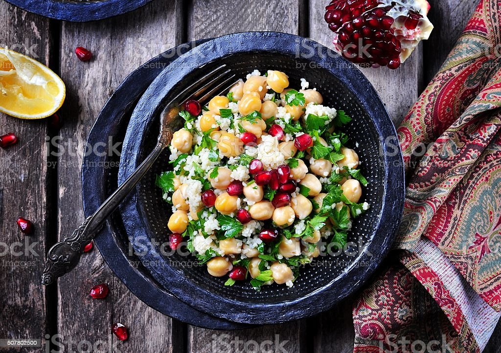 chickpea salad with couscous, parsley, olive oil and pomegranate stock photo