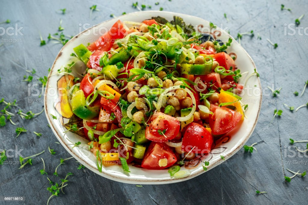 Chickpea salad with tomato, avocado, basil and olive oil stock photo