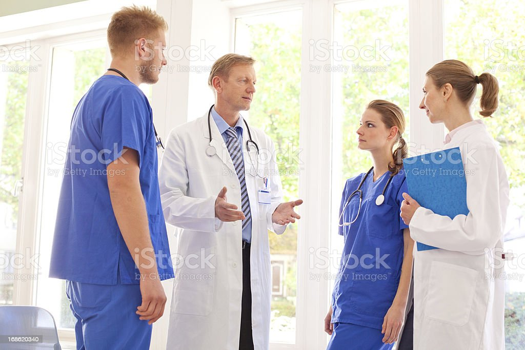 Chief Doctor speaking to his team stock photo
