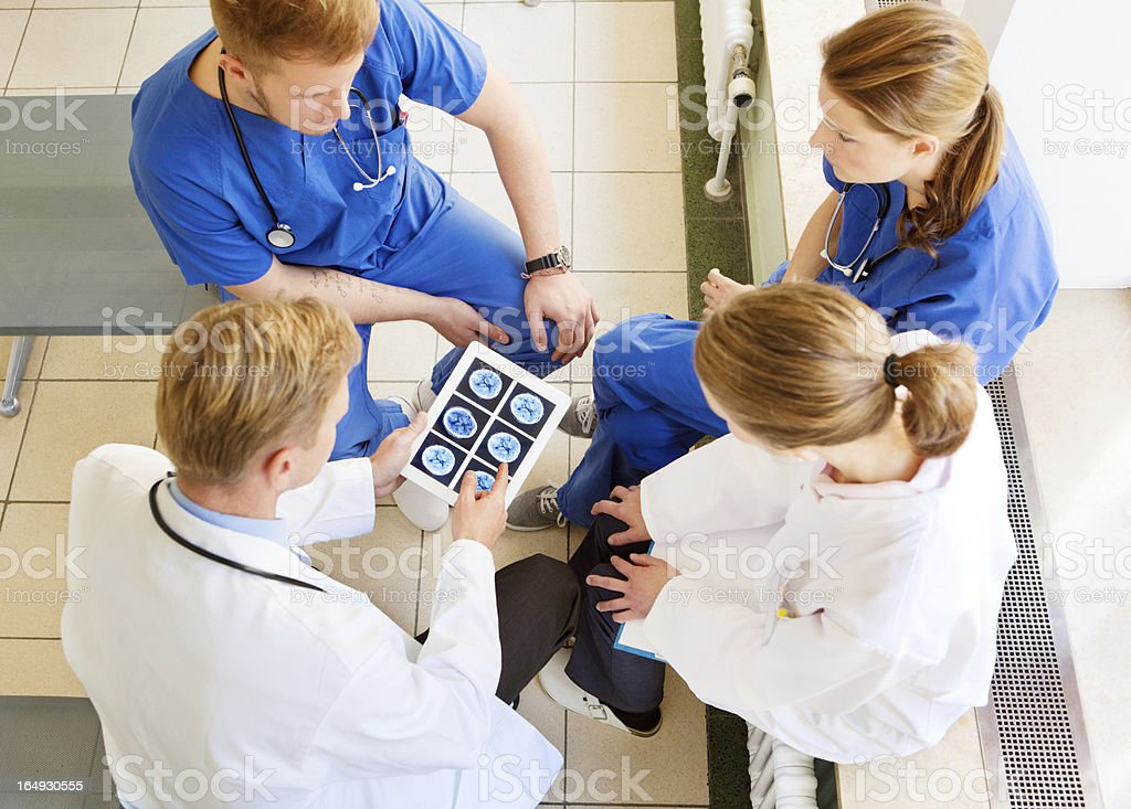 Chief Doctor speaking to his team with digital tablet stock photo