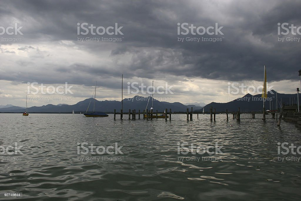 Chiemsee, Steg und Alpen unter dunklen Regenwolken stock photo
