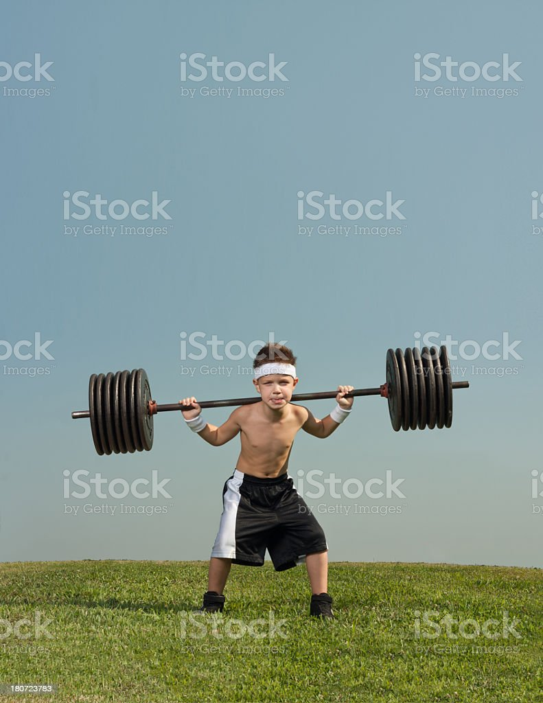 Child acting as bodybuilder lifting weights on grass stock photo