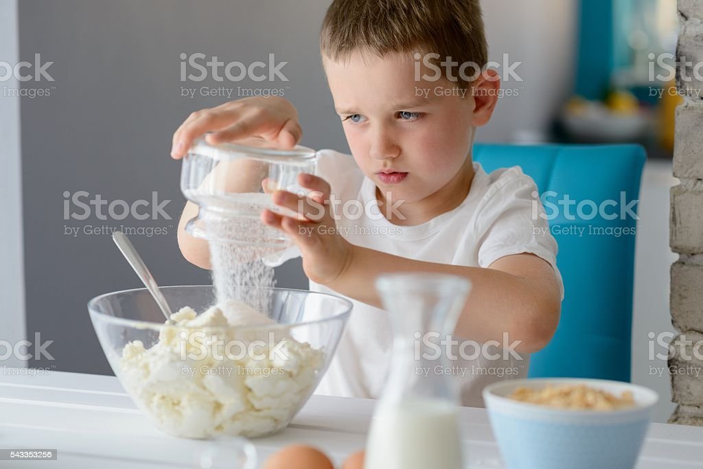 Child adding sugar to cottage cheese in a bowl. stock photo