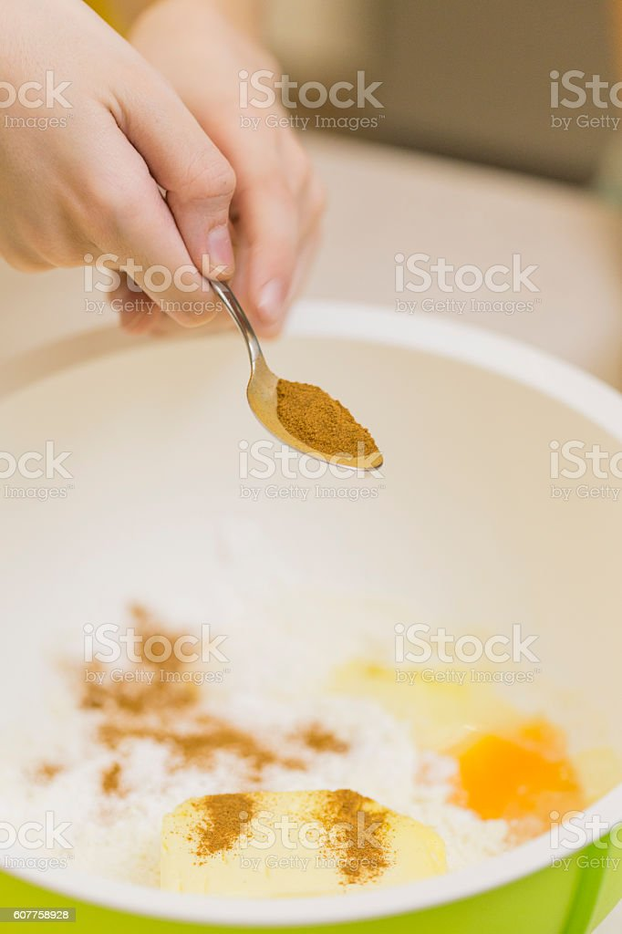 Child adds cinnamon into bowl stock photo