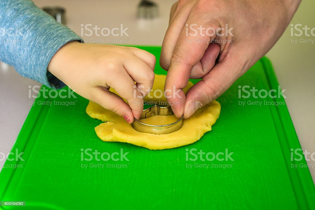 child and dad makes dough cookie cutters stock photo