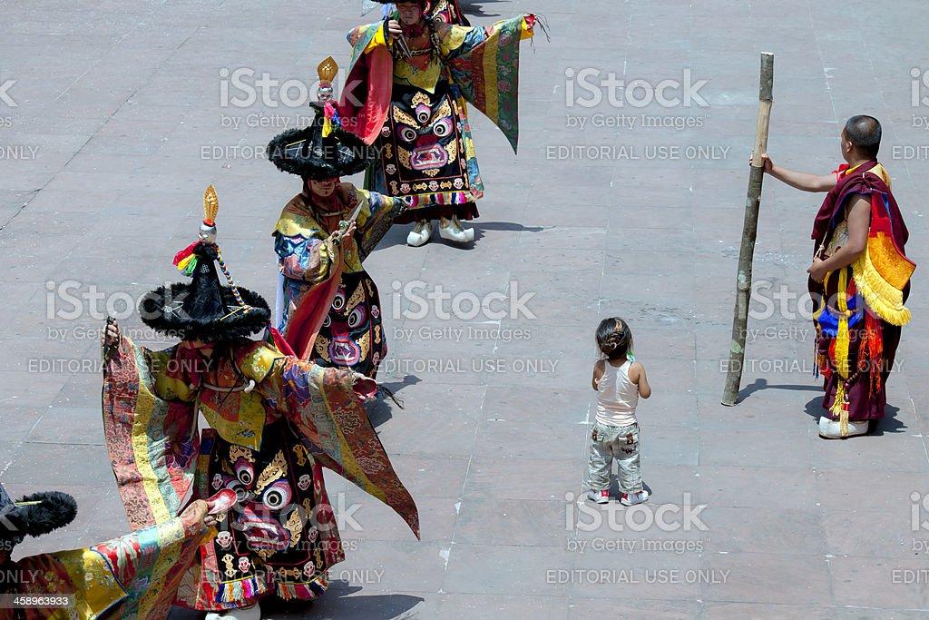 Child and Dancing Monks Rumtek Monastery Sikkim royalty-free stock photo