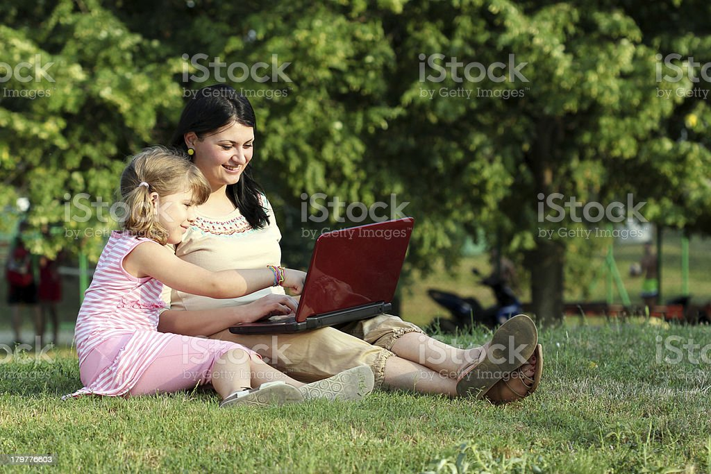 child and girl with laptop in park royalty-free stock photo