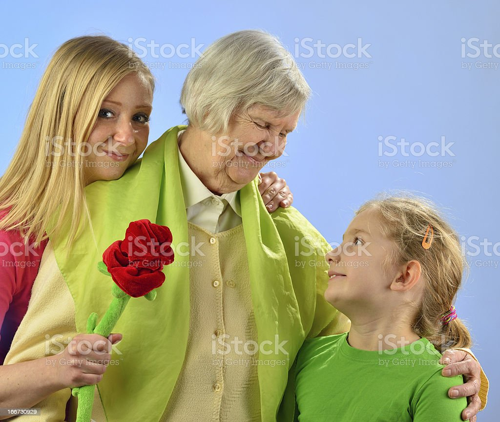 Child and grandchild give a gift senior woman. royalty-free stock photo