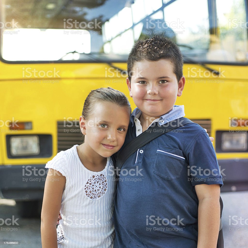 Child and his Girlfriend in Front a School Bus stock photo
