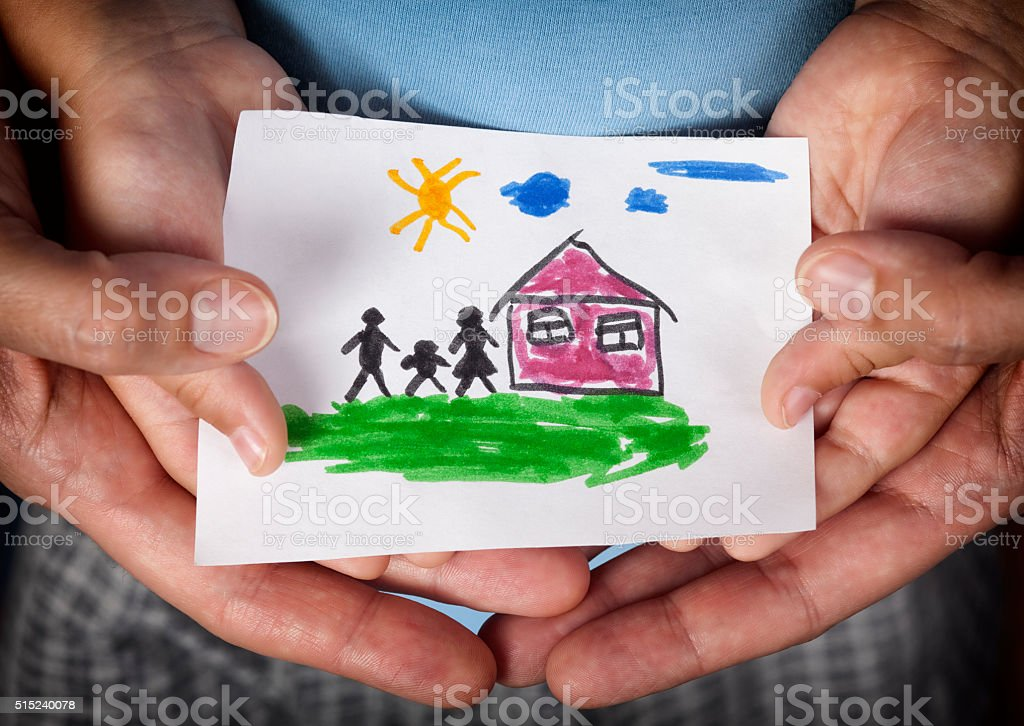 Child and his mom holding a drawn house with family stock photo