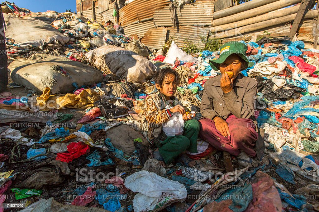 Child and his parents during break working on dump. stock photo