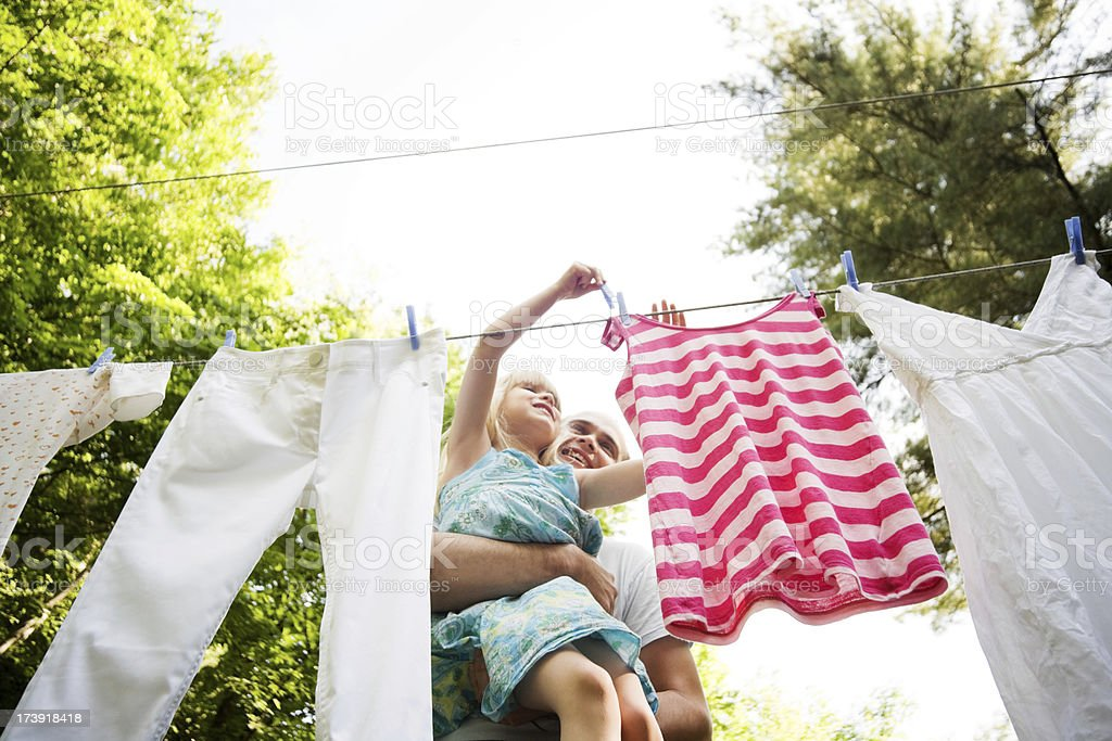 Child and Man Hanging Laundry in the Backyard royalty-free stock photo
