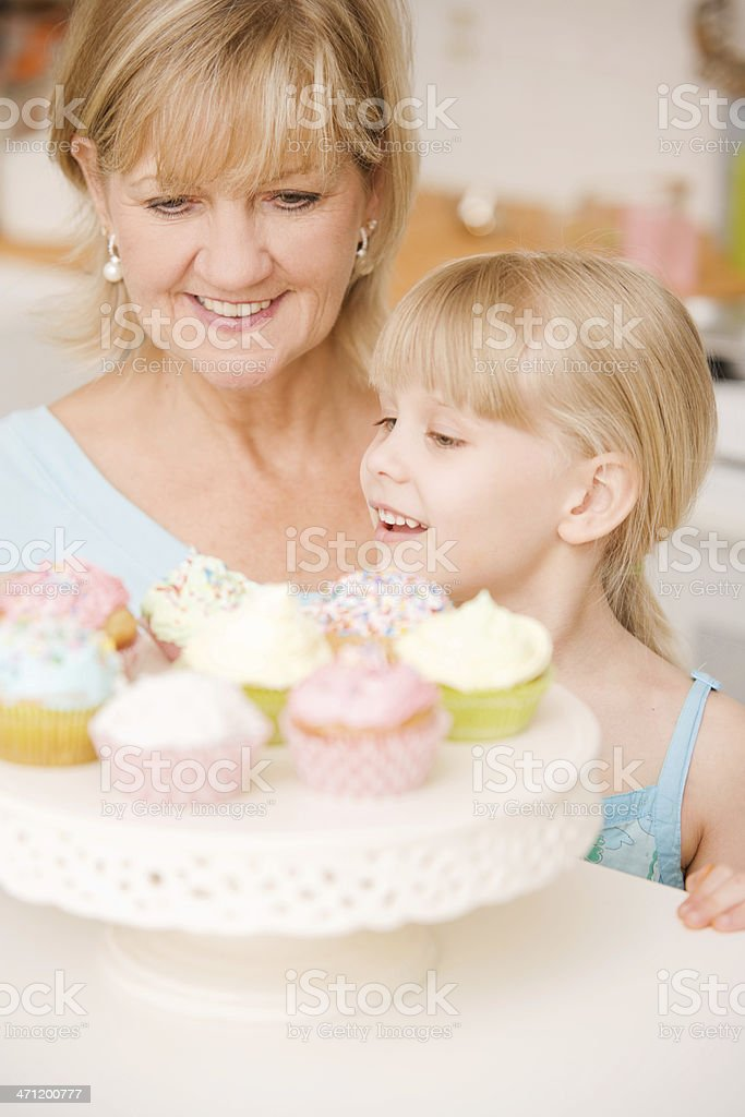 Child and Mature Woman Eating Cupcakes royalty-free stock photo